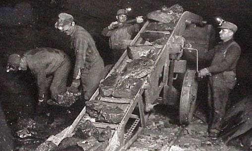 Miner Loading Coal by Hand inside the mine.