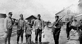 Three adult miners and one young lad pose for a picture with a policeman.