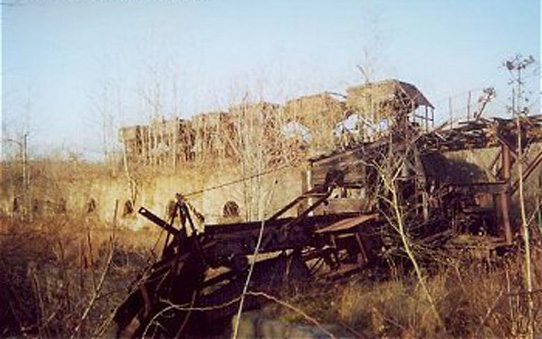 A coal extractor sits in ruins in front of Coke ovens with larry cars on the track above. The ovens are abandoned and overgrown with weeds.