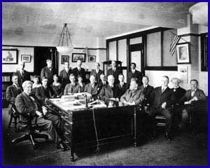 A large group of men sitting at and standing around a desk, posing for a group photograph.