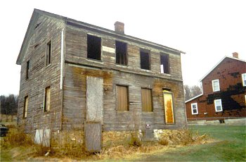 A color photograph of a faded two story wood house. Windows are missing and boards replace several of the openings.