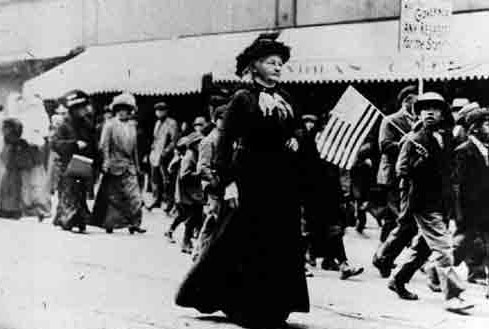 Mother Jones, wearing a black dress and hat, leads a group of protestors.