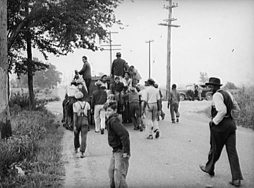 A group of children and men are walking down the road.