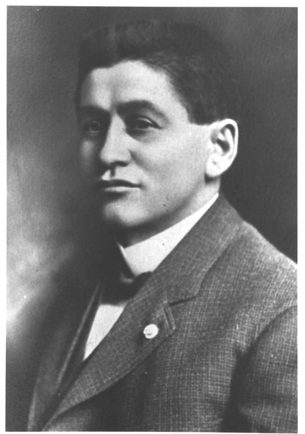 Photograph of Mack, head and shoulders, wearing a suit coat and bow tie.