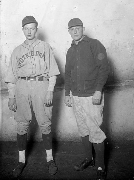 Two men standing side by side. The younger one wears a baseball uniform.