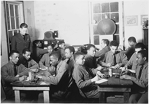 African-American men sit in a classroom.