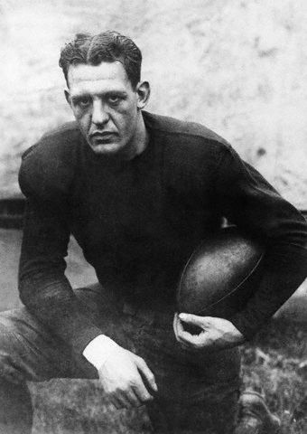 A man in uniform kneels while holding a football.