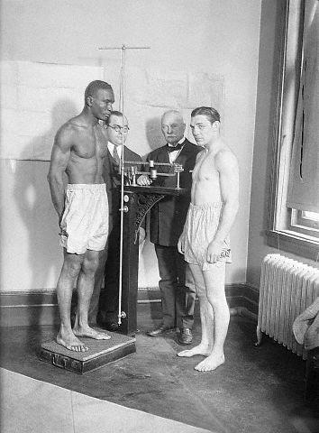 Left to right: Tiger Flowers, 157 1/2 pounds  (on scales), Bert Stand, Secretary of Boxing Commission; Com. Muldoon; and  Harry Greb 159 pounds;. The bout took place at Madison Square Garden.