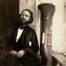 Joseph Leidy next to the tibia (lower leg bone) of Hadrosaurus foulkii, 1858.