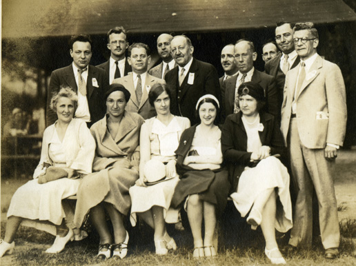 A group of people pose for a photograph. In the front row five, well-dressed women are seated in chairs. In the second row five men wearing suits are standing. The man in the middle of that row is James Maurer.In the third and last row, five men wearing suits are standing.