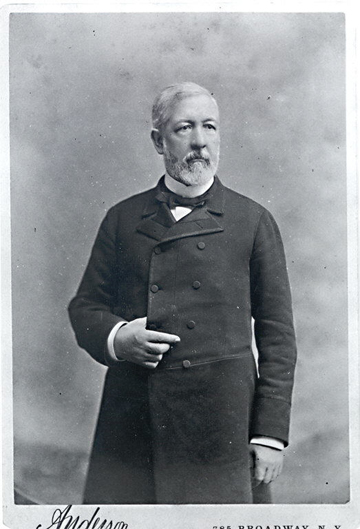 Albumen silver print of James Gillespie Blaine, ¾ length, right hand tucked inside of coat.