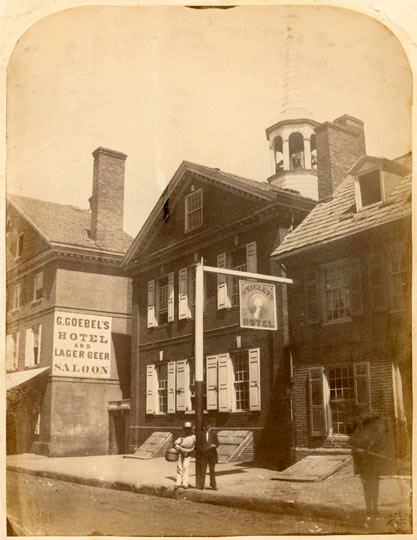"The building on street, surrounded by other buildings. Two men standing in front, leaning against a signpost. Horse in lower right-hand corner. Signs: ""G. Goebel's Hotel and Lager Beer Saloon"" ; ""Wrigley's Hotel."""