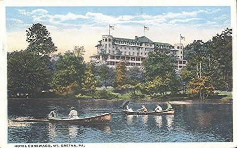 Colorful rowboats docked in the foreground, while an impressively grand Hotel Conewago stands in the background on shore.