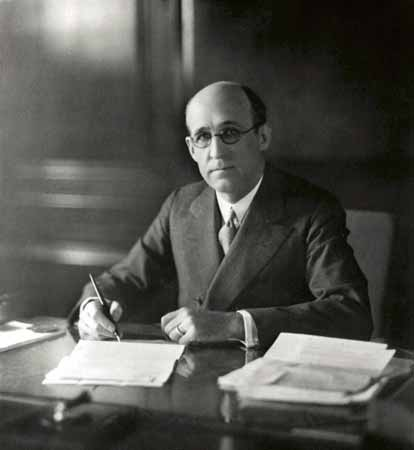 A portrait of Frank Phillips at a large desk in his office.