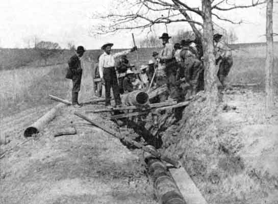 A black and white photograph of group of men dropping a large pipe into a shallow trench using wooden planks as levers.