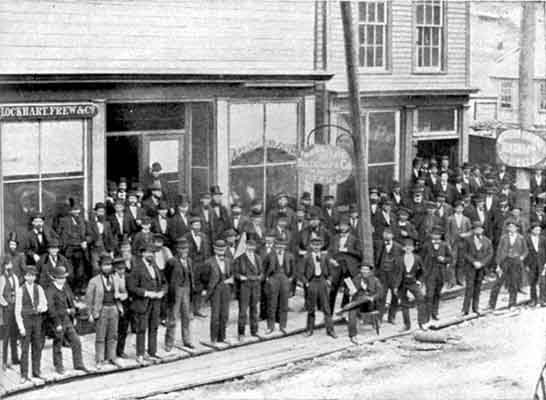 A group of several dozen men dressed in business suits and hats gather on a sidewalk in front of several stores in Oil City.