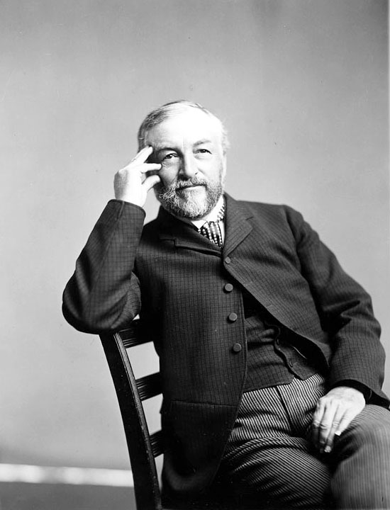 A man seated in a chair, wearing a suit.