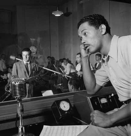 Billy Eckstine in a recording studio, leaning on a counter, with sheet music and a microphone in front of him. Visible through a window behind him is a small orchestra.