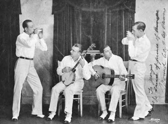 Four band members, all dressed in white, posing with their various instruments.