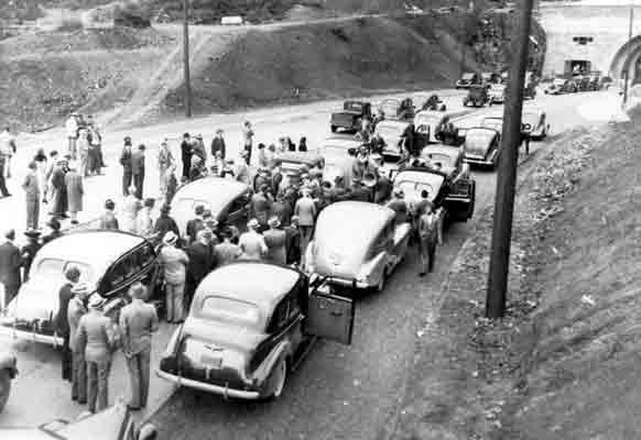 A line of cars and a crowd of people on a newly constructed highway, in front of a tunnel leading through a mountain.