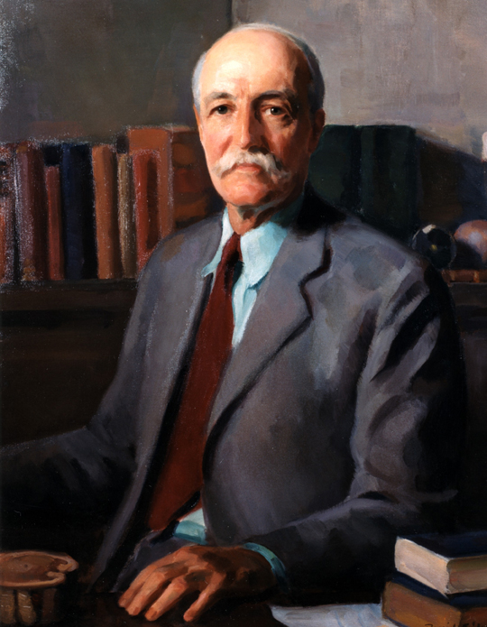 Pinchot wearing a suit, seated.