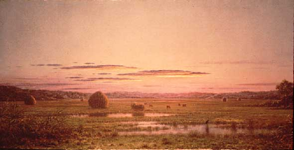 A colorful red sky sunset settles around the hay bales and cattle in the field. Patches of marshy water dot the landscape and birds appear to be feeding on the life that these patches provide.