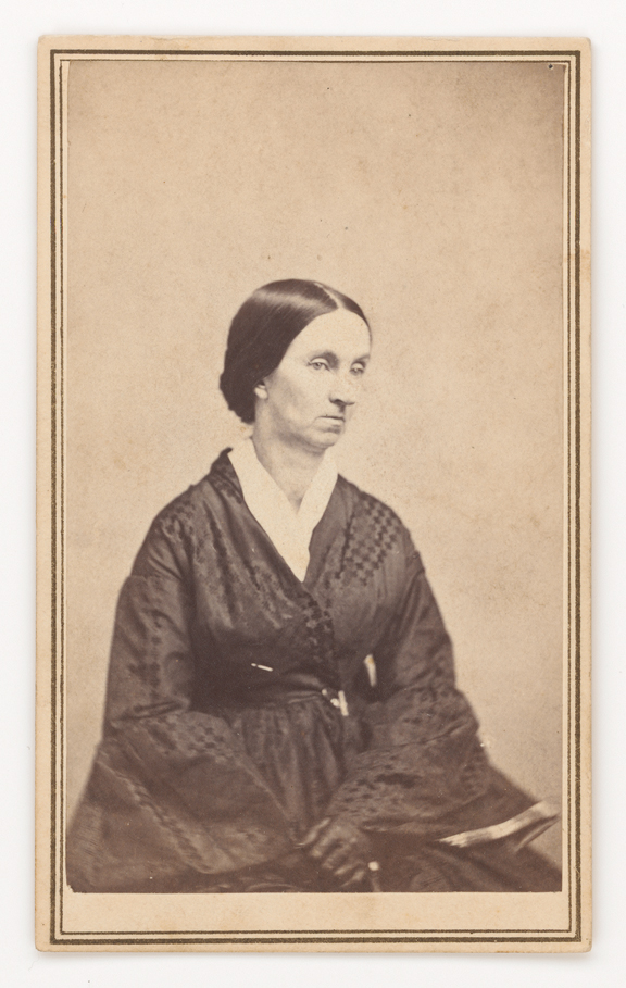 Albumen silver print of a lady with her her drawn back in a bun at the base of her neck. She is wearing a wrap style dress.