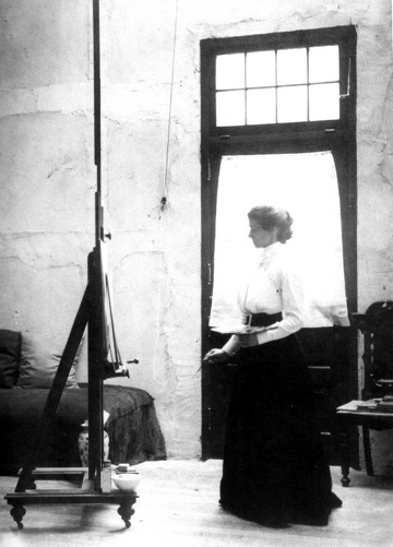 Black and white image of Violet Oakley in her studio, pallet in hand, standing in front of a mural.