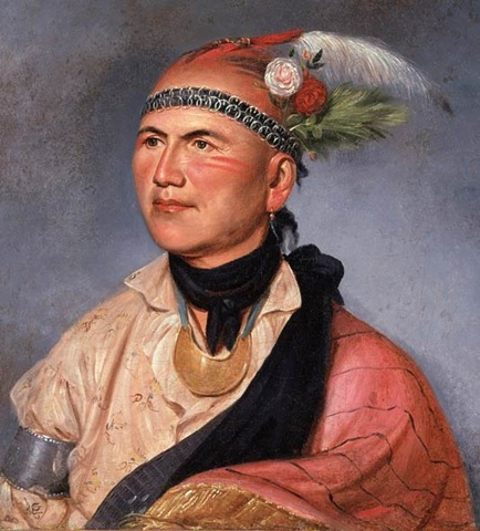 Oil on canvas of Joseph Brandt in colorful native American clothing and a head dress that includes a band and several green and white feathers. Small amounts of war paint adorn his cheeks.
