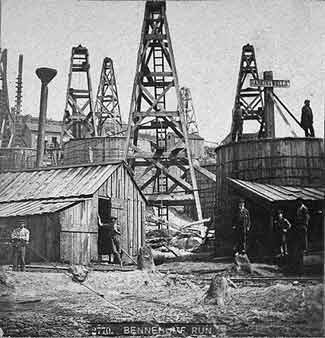 Early oil fields had storage tanks and company buildings close to the oil derricks, as shown in this photo of Bennehoff Run. The danger of this setup was demonstrated when lightning struck a pipe at Bennehoff in July 1866, igniting an adjacent tank. The tank exploded almost immediately, releasing burning oil down the run, and destroying as many as 30 derricks and adjacent tanks.