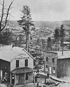 A view of Pithole from First Street, looking east. Note the field of oil derricks. The large white building visible in the distance is the Bonta House Hotel. At its peak, Pithole had 57 such hotels.