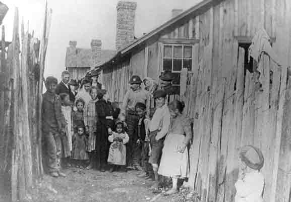 "A group of adults and children assemble for this photograph between two plank fences in their ""patch"" town"
