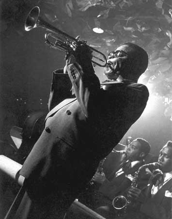 A black and white photo of Dizzy Gillespie playing the trumpet in a club. Visible in the background are members of his band.