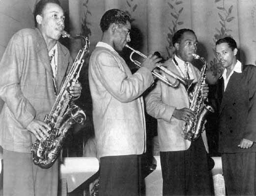 A black and white photograph of a line of four musicians on stage; two hold saxophones, one holds a trumpet.