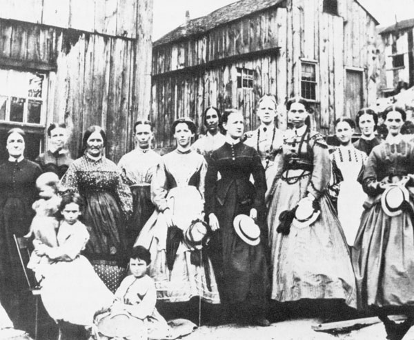 """Twelve women and three girls dressed in """"Sunday"""" clothes pose in front of weathered clapboard houses."""