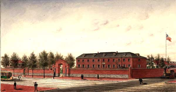 Red brick building sitting behind a high red brick wall with two gates facing Grays Ferry Road. A white building also sits behind the wall. The United States flag flies on a mast. To the right   a train engine advances with smoke billowing from the stack   The horse drawn car tracks and train tracks cross at the corner. Seven adult male pedestrians are in the scene.