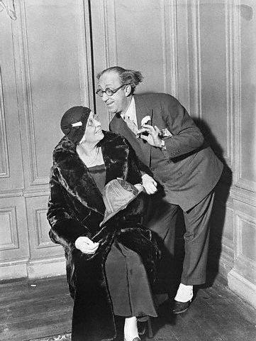 American comedian Ed Wynn bends down to tell his mother a comical story.