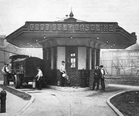 An antique truck is parked next to a small, octagonal shaped building. Several people are standing around the building, filling small tanks.