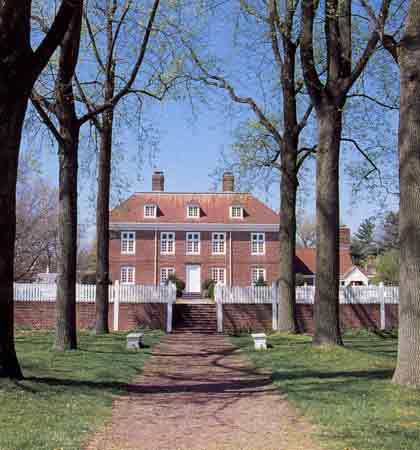 A color photograph of a tree-lined path leading to a brick Georgian-style manor house.