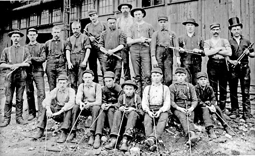 Men and boy wire drawers pose with their tools outside a wire factory.