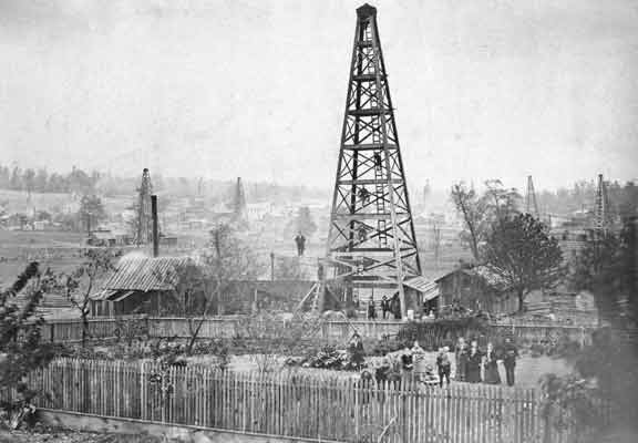 A group of men and women pose within the fenced perimeter of a back yard. Directly behind the fence is a tall oil derrick. More men have climbed the derrick and are posing at varying heights.