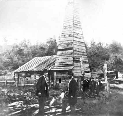 Two gentlemen dressed in suits, one in a top hat, stand in front of a tall oil derrick that is enclosed with wooden planks.