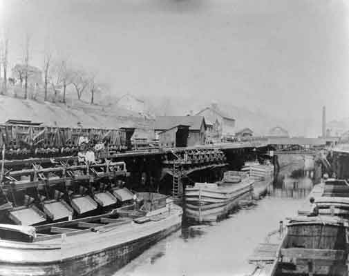 Railroad cars on docks above canal boats in the canal basin. Several canal boats are visible, waiting to be filled.
