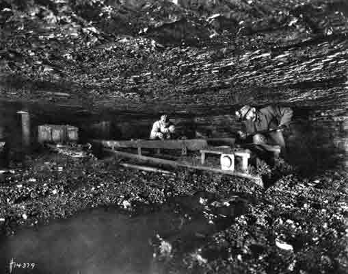 Two miners are working over a conveyor belt in a mine. Both men are kneeling, and their heads and shoulders are against the ceiling of the mine.