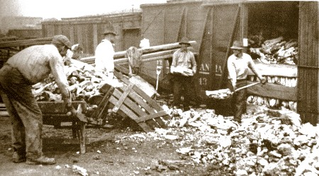 Men loading coke into wooden railroad box cars.