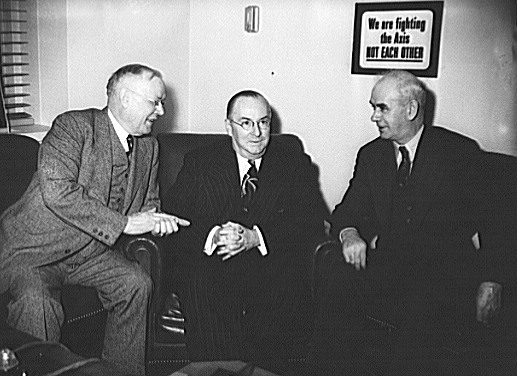 """Lee Pressman, Congress of Industrial Organizations (CIO) counselor; Philip Murray, CIO president; and Harold Ruttenberg (speaking), research director, United Steel Workers (USW), at the """"Little Steel"""" hearing held by the War Labor Board at the Hotel Washington in Washington, D.C., July 1."""