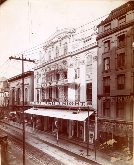 "The building with signs on front from top of third floor windows to bottom of second: ""This week Hoyt's A Day and a Night"". To the left of the theater is the Free Library and to the right, a piano shop with letters standing out from the building: ""Steinway"" both above the doorway and on the second floor. Streetcar tracks on Chestnut. Horse and carriage on street. Pole on the opposite side of the street with many electrical wires."