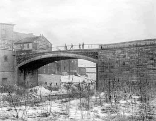 Sepia-toned photograph of Dunlap Creek Iron Bridge taken from the ground a distance away. Several men are standing on the bridge and a few buildings are apparent on the left side.