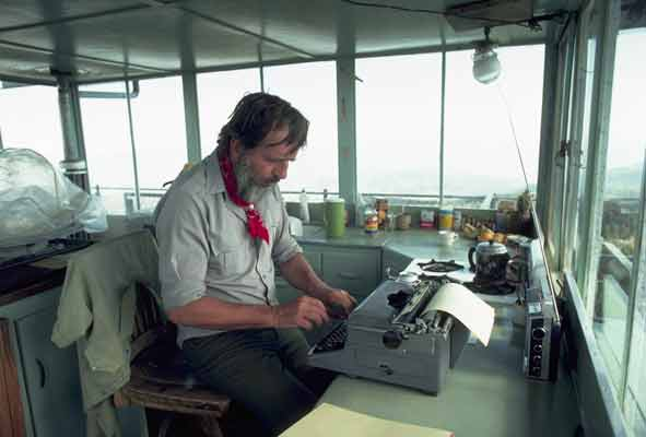 Edward Abbey working at a typewriter, surrounded by the windows and expansive views of his Arizona fire tower.