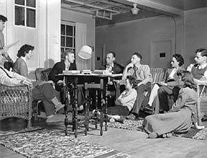 Image of men and women sitting in chairs, on the floor, and standing while attending a meeting